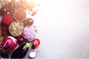 Purple vegetables, fruits on grey background. Violet eggplant, beets, cauliflower, purple beans, plums, onion, cabbage, grape, quinoa, rice. Ingredients for cooking, copy space, top view, flat lay