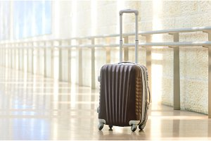 Packed travel suitcase, airport. Summer holiday and vacation concept. Traveler baggage, brown luggage in empty hall interior. Copy space