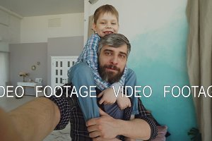 Point of view shot of bearded man and his son sitting on his shoulders recording video selfie, talking and laughing at home. Happy family and modern technology concept.