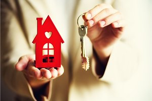 Female hands holding small red house and keys. Real estate agent offer you house or apartment. Property insurance and security concept. Copy space