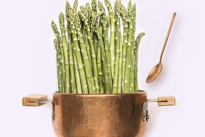 Asparagus in cooking pot with spoon