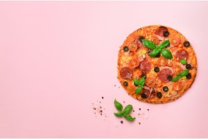 Delicious italian pizza, basil leaves, salt, pepper on pink background with copyspace. Top view. Banner. Pattern for minimal style. Pop art design, creative concept
