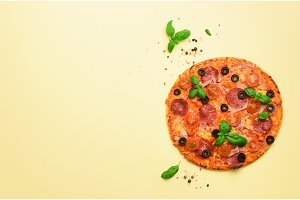 Delicious italian pizza, basil leaves, salt, pepper on yellow background with copyspace. Top view. Banner. Pattern for minimal style. Pop art design, creative concept