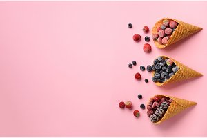 Frozen berries - strawberry, blueberry, blackberry, raspberry in waffle cones on pink background. Top view. Banner. Pattern for minimal style. Pop art design, creative concept