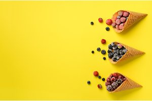Frozen berries - strawberry, blueberry, blackberry, raspberry in waffle cones on yellow background. Top view. Banner. Pattern for minimal style. Pop art design, creative concept