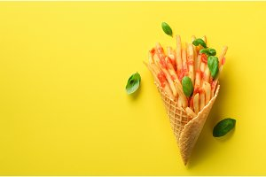 Fried potatoes in waffle cones on yellow background. Hot salty french fries with sauce, basil leaves. Fast food, junk food, diet concept. Top view. Minimal style. Pop art design, creative concept