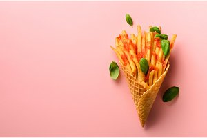Fried potatoes in waffle cones on pink background. Hot salty french fries with sauce, basil leaves. Fast food, junk food, diet concept. Top view. Minimal style. Pop art design, creative concept
