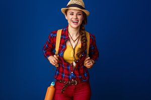 happy fit woman hiker with backpack against blue background