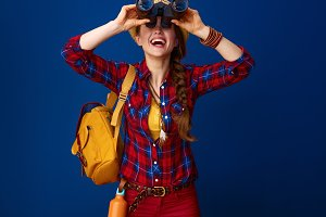 tourist woman on blue background looking up through binoculars