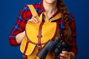 happy tourist woman on blue background holding binoculars