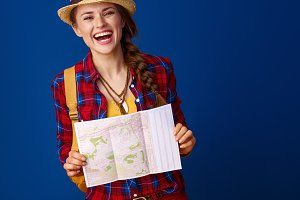 smiling fit traveller woman on blue background with map