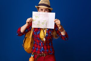 traveller woman against blue background hiding behind map