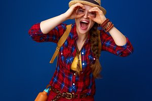 smiling tourist woman looking through binocular shaped hands
