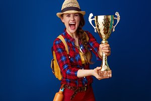 young excited woman hiker isolated on blue showing goblet