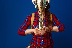 traveller woman on blue background hiding behind goblet