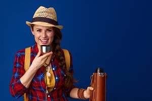 happy woman hiker drinking hot beverage from thermos bottle
