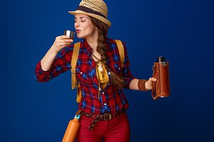 tourist woman drinking hot beverage from thermos bottle