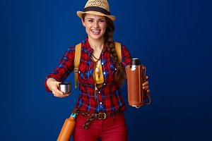 smiling woman hiker proposing hot beverage from thermos bottle