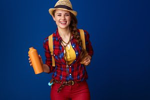 woman hiker isolated on blue background with water bottle