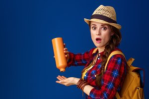 surprised young tourist woman having left no water in bottle