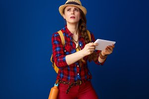 concerned woman hiker with tablet PC having orientation problem
