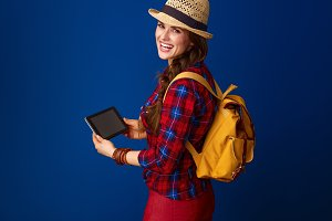 happy tourist woman against blue background using tablet PC