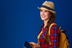 smiling traveller woman with tablet PC looking into distance