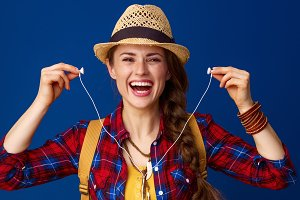 happy traveller woman isolated on blue holding headphones