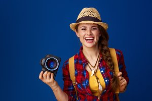 traveller woman isolated on blue background with digital camera