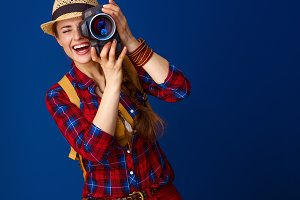 happy active woman hiker with modern DSLR camera taking photo