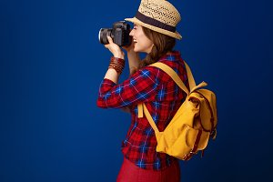 tourist woman isolated on blue with DSLR camera taking photo