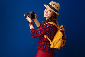 smiling young woman hiker with modern DSLR camera taking photo