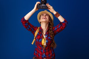 woman hiker on blue background with DSLR camera taking photo
