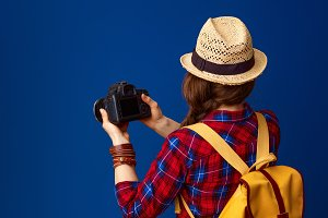 tourist woman on blue background with DSLR camera taking photo