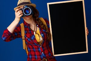 traveller woman with blackboard taking photo with digital camera