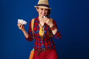 happy traveller woman against blue background having meal break