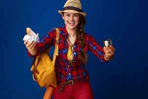happy young tourist woman giving sandwich and hot beverage