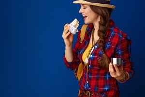 smiling fit traveller woman eating sandwich with hot beverage