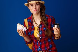 adventure traveller woman eating sandwich with hot beverage