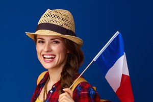 happy woman hiker on blue background with flag of France