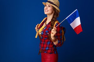 happy traveller woman with flag of France looking into distance