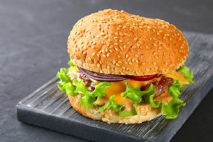 Tasty homemade burger consisting of bun, patties, salad, red onion and tomato on a dark black concrete background, table.