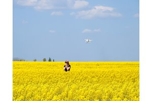 Dron flies after the girl. Shooting with a drone in the field. A girl in a black dress in a field of flowering rape.