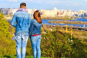 couple stands on a hillside and looks at the panorama of the city