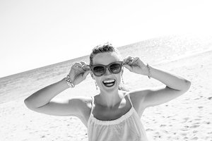 happy modern woman on seashore holding sunglasses