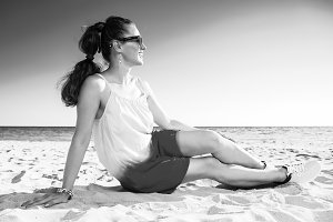 smiling trendy woman sitting on beach