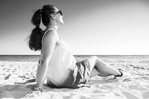happy trendy woman on beach looking into distance