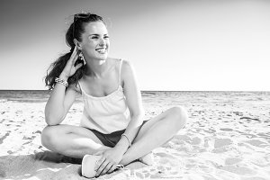 smiling trendy woman on seashore looking at copy space