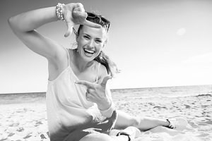 happy modern woman on beach framing with hands