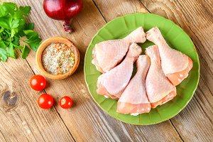 Raw chicken legs on a cutting board on an old wooden table.